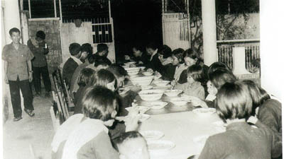 """Duch arrivant à un repas de mariage. Cette photo a été présentée par les co-procureurs lundi 22 juin 2009 au tribunal. Dans le livre réalisé par le DC-Cam sur l'histoire du Kampuchéa démocratique, cette image est légendée : """"Personnel de Tuol Sleng mangeant en communauté"""". (Tuol Sleng Genocide Museum Archives)"""