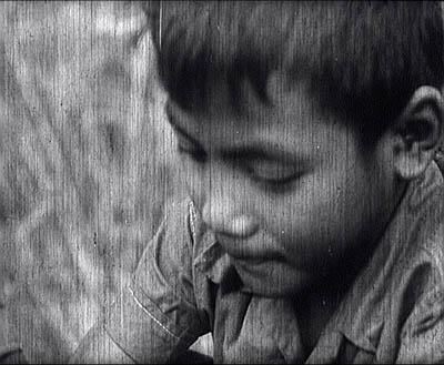 """Phal, le jeune garçon découvert à S21 par les troupes de libération est filmé avec son frère et les deux autres enfants dans """"Les enfants du Cambodge"""". Le film n'est pas daté. Les images sont en consultation libre au centre Bophana à Phnom Penh. (Direction du cinéma)"""