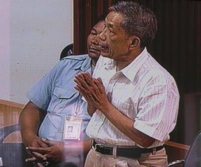 Posture de Duch quand il authentifie des documents. C'est notamment ainsi qu'il reconnaît la détention à S21 de Norng Chanphal. (Anne-Laure Porée)