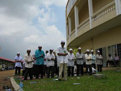 Dans le public du tribunal ce lundi 17 août, de nombreux Chams amenés par le Centre de documentation du Cambodge. A midi, ils font leurs ablutions et entament leur prière sur le petit espace de pelouse devant la salle d'audience. (Anne-Laure Porée)